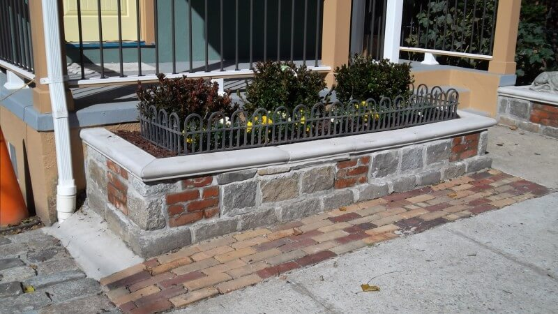 In the other, smaller shrubs and flowers are planted and surrounded by a small iron fence. The fence is packed in by cedar wood chips.