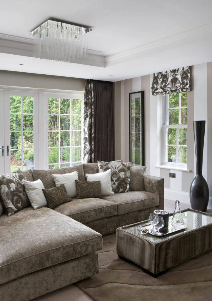 A multi-textured elegant living room. The sofa is in soft gray suede, the glass-topped coffee table is upholstered in a coordinating corduroy, and the thick drapes have a bold pattern. The result is an elegant, varied design with a few modern, glass elements, including the chandelier. To the right is an enormously tall charcoal gray vase.