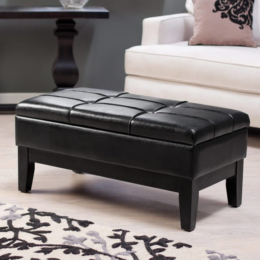 This black leather bench ottoman stands button tufted leather over a visible dark wood frame with taller legs. The cushioned lid conceals lengthy storage space.