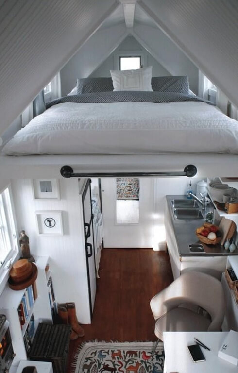 A loft bed makes the most out of this sharply sloped attic space. Placing the bed in the loft creates more space for a small kitchenette and office space below.