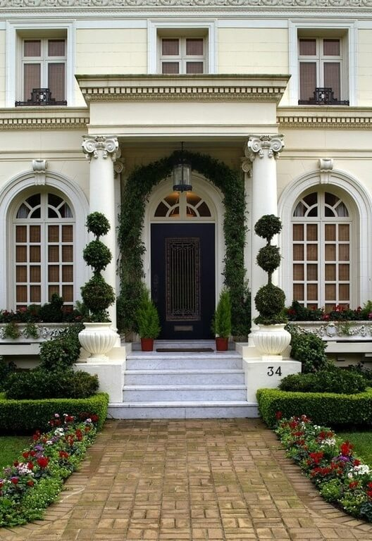 Marble steps lead to an intricately carved front door framed by greenery.