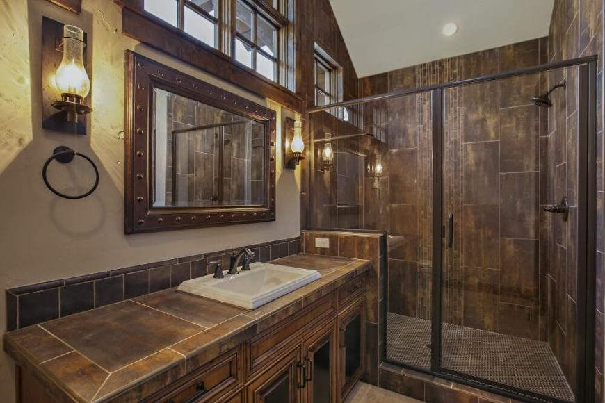 The adjoining bathroom in bronzy tile and accents. The wall sconces are made to look like old-fashioned gas lights, and the glass-enclosed tile shower has brushed nickel fixtures. A stripe of vertical tiles in the center of the shower adds visual interest. A series of high windows allow natural light into the bathroom without sacrificing privacy.