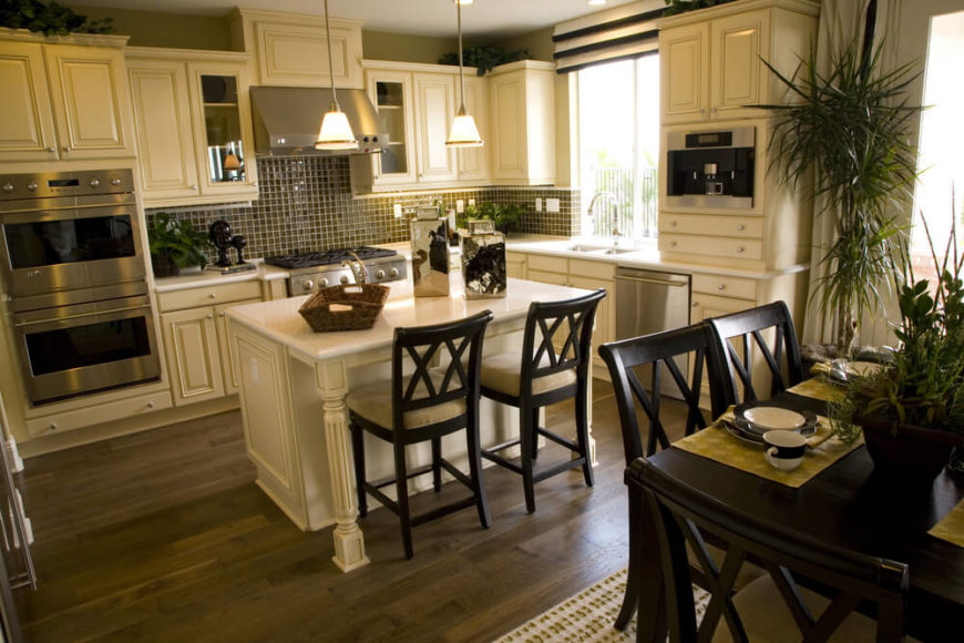 A white kitchen with glass-tile backsplash and hardwood flooring. A small kitchen island has chairs that match those of the dining set just behind them.