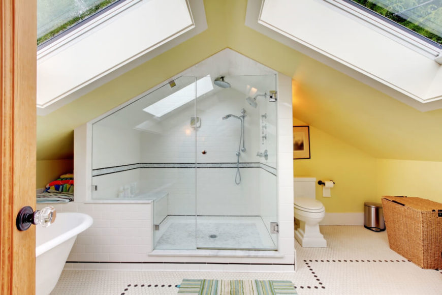 An attic bathroom under a pointed roof with two enormous skylights. The huge shower enclosure includes a bench and its own skylight. To the left is a free-standing soaking tub and a nook for towels.