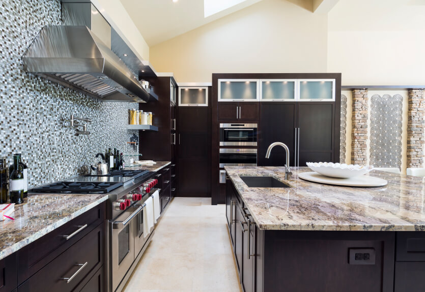 A dark kitchen with marble countertops and a large amount of glass mosaic tile on the wall above the range and extending on either side.