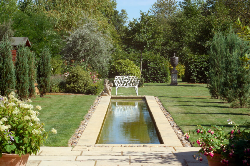 A more cosmopolitan pool stretching out into the yard from the patio and ending in a white bench and angle statue. Evergreens and other large trees and bushes line either side of the yard.