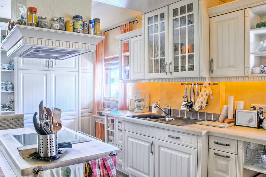 A charming kitchen in white with a center range on the island. The backsplash consists of one layer of gray tiles below the yellow walls.