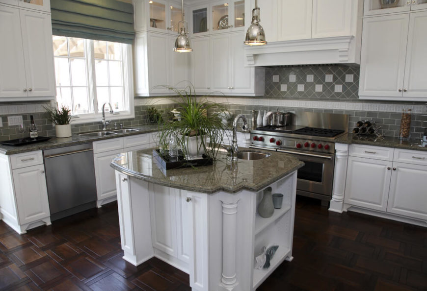 A white kitchen with olive-green tile backsplash and an ornate dark-wood floor. The top wall cabinets are backlit and used for display.