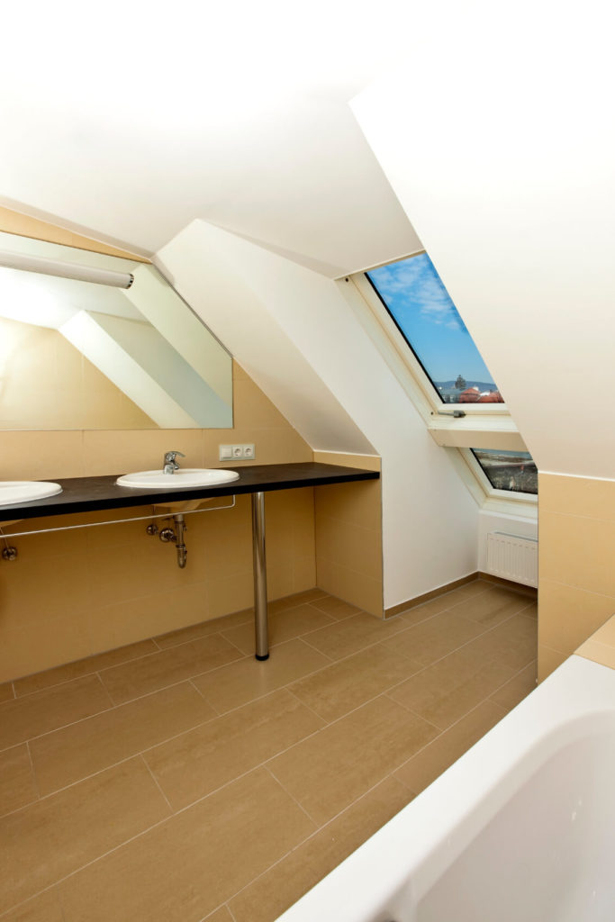 A narrow attic bathroom in beige with an industrial-style vanity that houses two traditional sinks. To the right is a small alcove with a skylight.