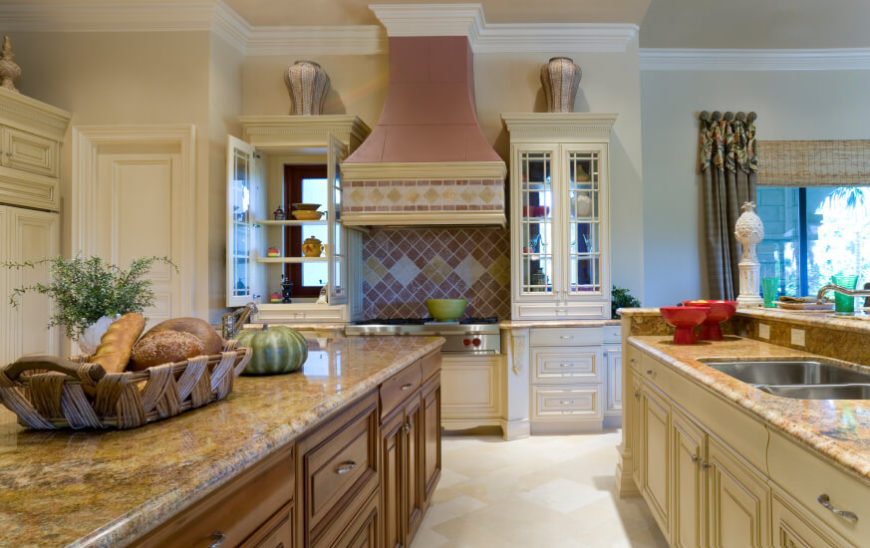 The only backsplash in this country kitchen is behind the stove, with a strip of tile along the pink and yellow vent hood. The pastels of the stone tiles pick up the warmer shades in the granite countertops.