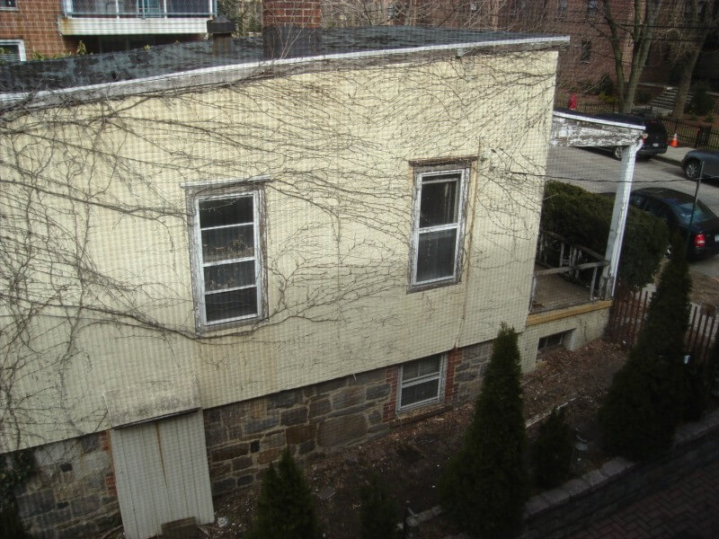 A view of the roof and left side of the home from above, showing the poor state of the roof and damage to the siding. Several of the basement windows are also covered or boarded up.