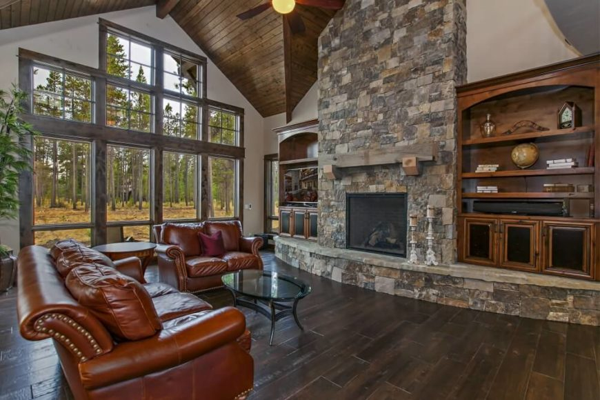 The grand room of this home has a massive built-in stone fireplace with a rustic wooden mantel. Matching bookcases are built on either side of the fireplace on the curved hearth. Behind the dusky red leather sofas are a massive series of windows that follow the shape of the wall for a grand appearance from both the exterior and the interior.
