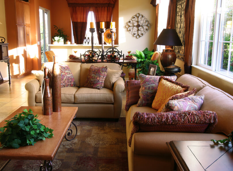 A living room with southwestern flair and fantastic patterned throw pillows on the beige sofa and loveseat. The open-concept space also includes a dining room. A hallway runs along the left side of the room past the living room, dining room, and kitchen area and leads outside to the deck.