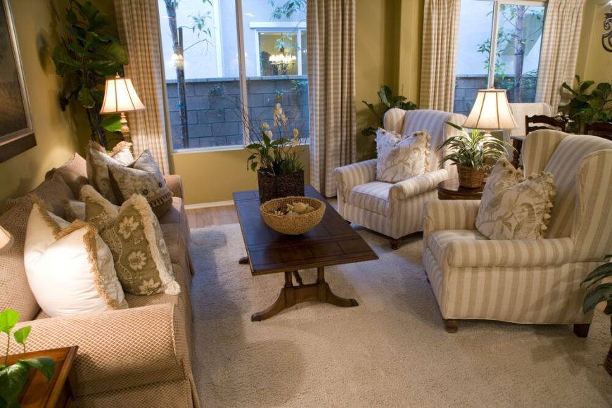 A small living room created by sectioning off a bit of a larger room to create a dedicated visiting seating arrangement. Tasseled pillows and layered patterns add visual interest to the light-colored space. The dark wood coffee table provides contrast. Spacious windows let in lots of natural light.