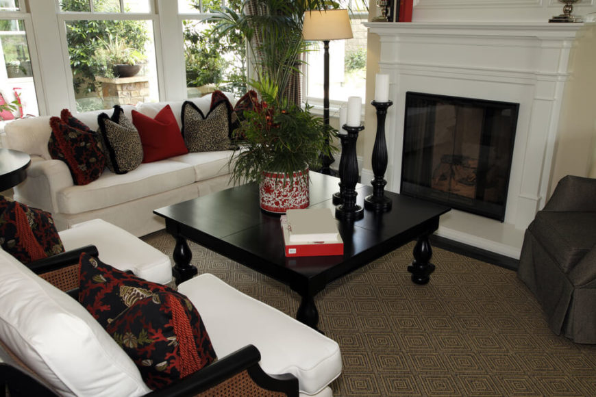 A small living room with a tall, narrow fireplace and white furniture. The black coffee table has ornate legs. The carpet has a geometric pattern. Accents include tall candles, animal prints, tasseled pillows, and a large green centerpiece. The contrast between the table and cushions is striking.
