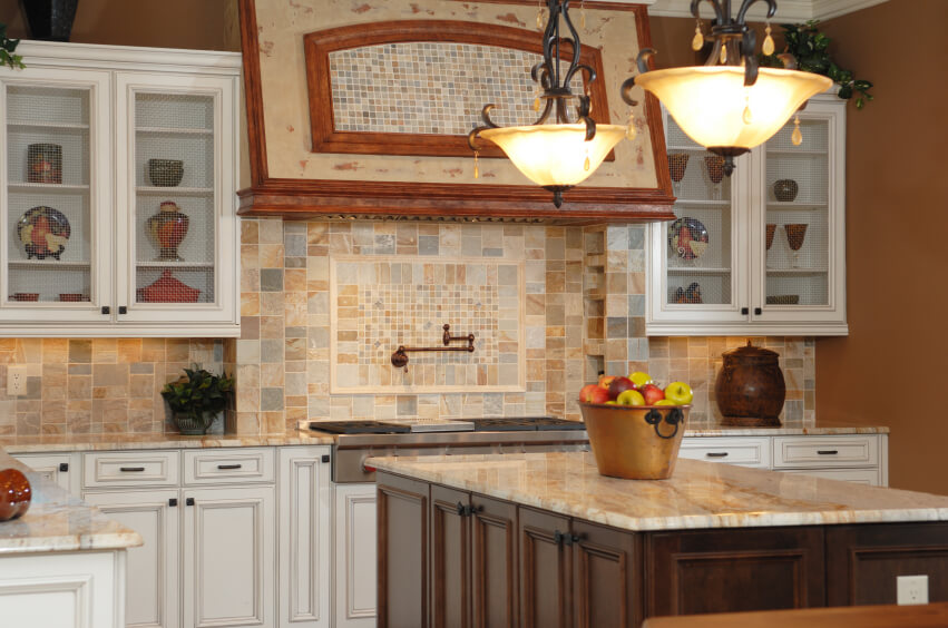 A multi-colored stone backsplash with tiles in varying shapes. A section in the center above the stove is in much smaller square tiles with a bronze faucet extending from it. The square pattern is repeated above the stove on the small vent hood.