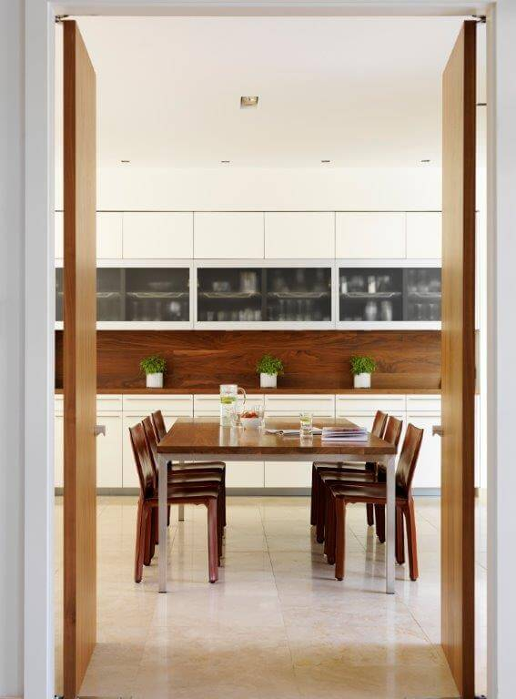 Double doors leading from the entryway look in on the breakfast table.