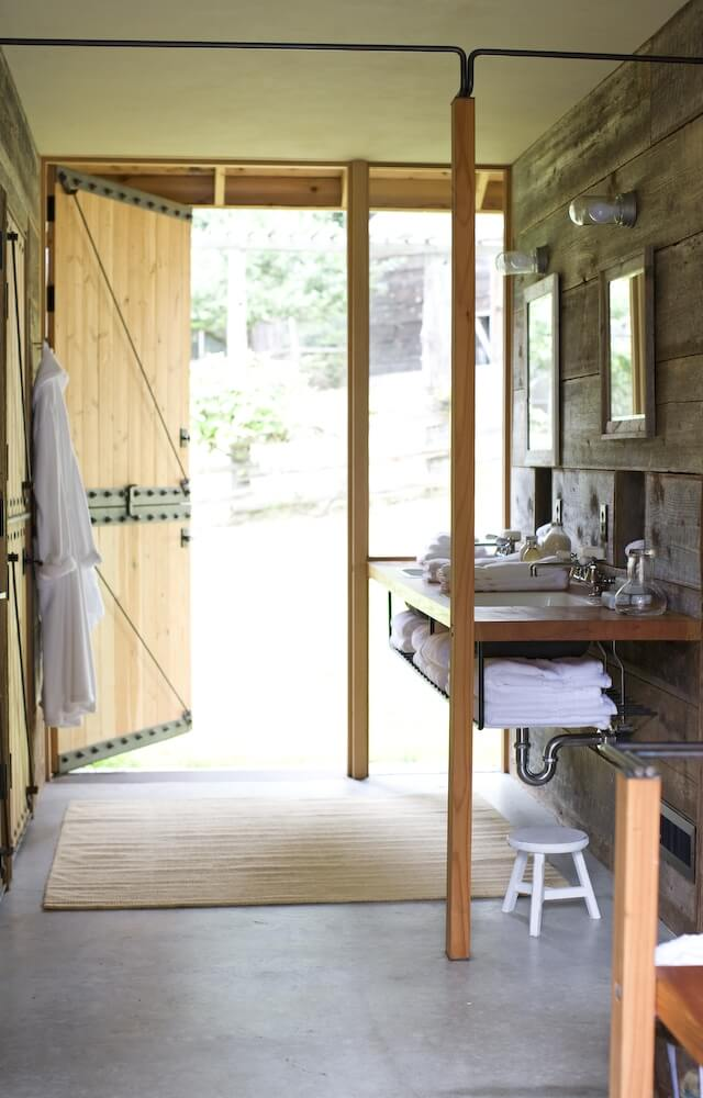 One of the bathrooms in the barn, with concrete flooring and a vanity with towel storage beneath. Like the bunk room, one of the original barn doors leads directly outside.