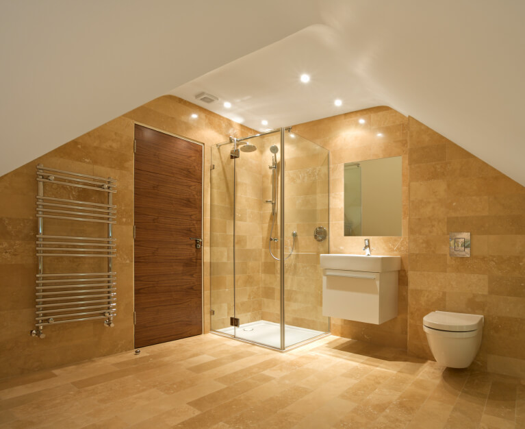 A smaller bathroom beneath a sloped roof in golden-toned tile. The shower, sink, and commode are lined up on the far wall, adjacent to the door and towel rack.