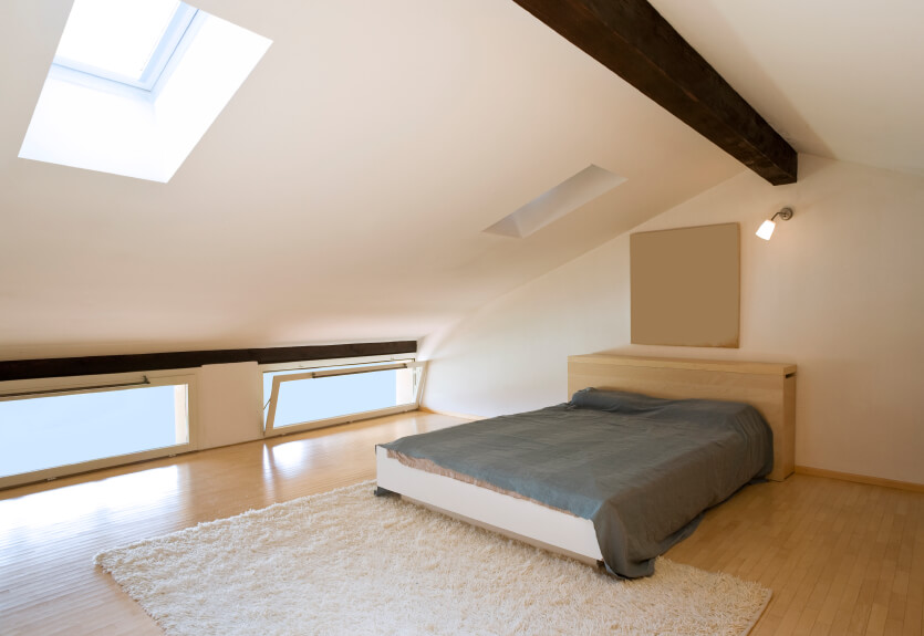 Hopper windows and a softly angled ceiling accentuate the arch of this bedroom. Clean lines and a soft rug continue the minimalist theme of slim, low-profile furniture and natural materials.