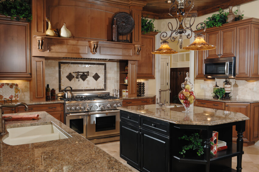 A very light cream ceramic tile backsplash brightens up the rich wood cabinets and the beige granite countertops.