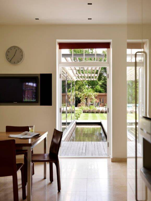 Through the doorway next to the breakfast table is a pair of French doors that lead out into the garden. Visible is the wooden planking that serves as a footbridge across the water feature.