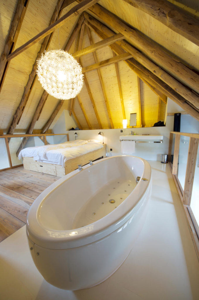 A rustic attic bedroom enclosed by glass barriers on either side of the loft. A soaking tub on white tile runs along the right portion of this bedroom, combining the usually separate bedroom and bathroom into one neat space.