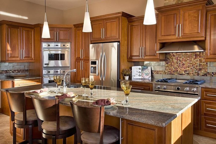 This luxurious kitchen has two different materials in the backsplash. A metallic stone subway-style tile with a strip of bold, glistening 1 inch mosaic tiles in gold, red, and orange.