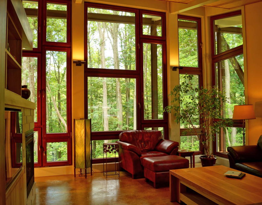 Behind the half wall of the dining room the various windows continue into the living room, which has a small set of seating in red and chocolate brown leather.