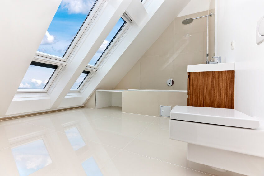 An all white bathroom with a slanted roof with plenty of windows. The natural wood vanity provides a sharp contrast to the tub and commode.