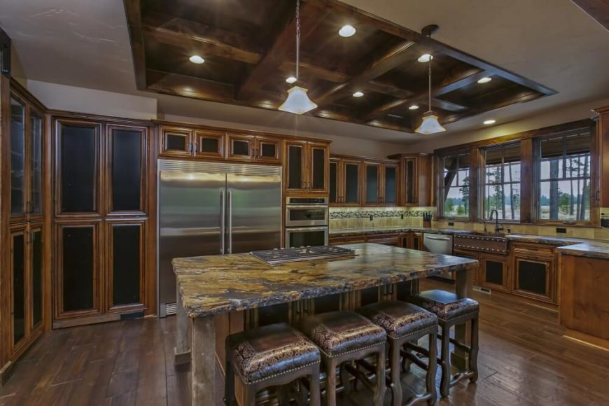 A closer look at the second kitchen layout, showing the black centers of the rich wood cabinetry and the shades of brown on the marble countertops. The four barstools lined up on one end of the island are faux leather with an ornate swirling design around the edge. Also of note is the coffered ceiling in the center with one pot light in each square.