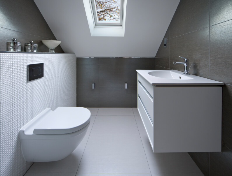 A small white and gray bathroom with textured tile behind the commode. The sink is directly across from the commode.