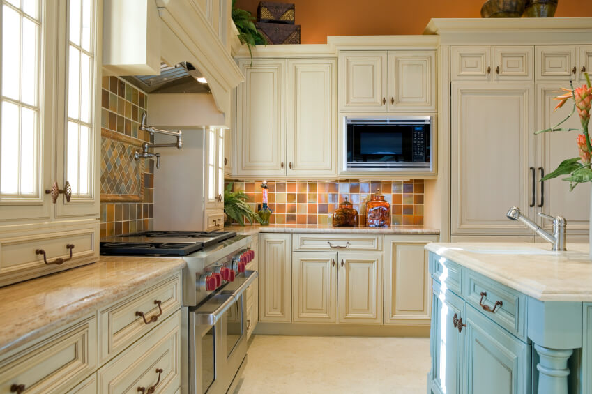 A country kitchen with a light blue island and multicolored ceramic tiles for the backsplash. Like many of the other kitchens in this collection, a coordinating centerpiece above the stove adds visual interest to the larger section of backsplash.