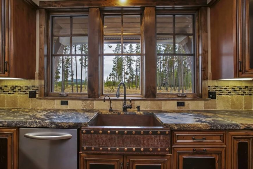 A close up on the farmhouse sink, showing the textured dusky red sink with two strips of nail head trim along the front. Three windows sit behind the sink, showing a private view of the pine forest and the grasslands beyond.