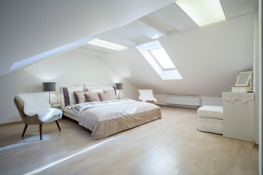 Primary bedroom in large attic with skylights