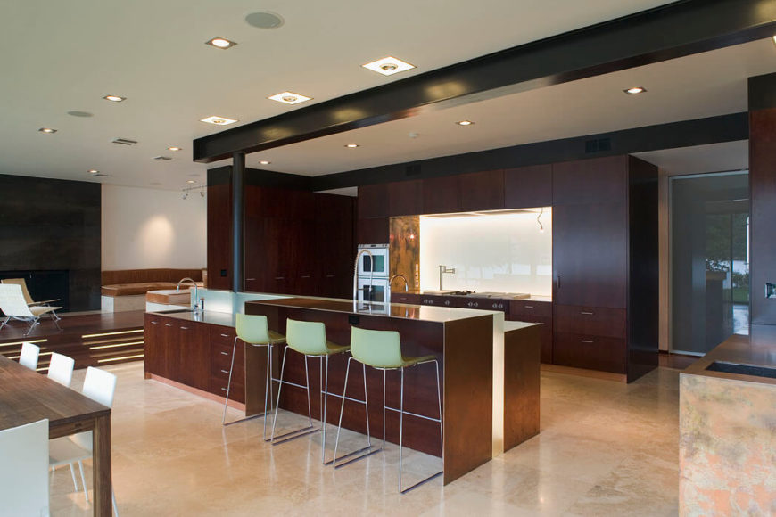 The brassy finish of the kitchen island is repeated around the perimeter of the cooking area alcove. The backsplash is a glossy white.