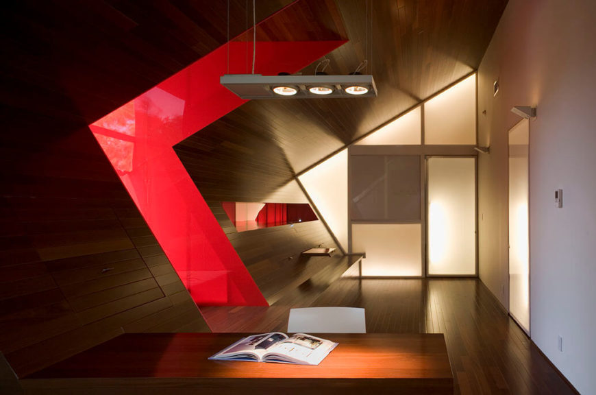 The home office is smooth and gives the appearance of having been carved out of a single piece of wood. The desk and retractable game table slide back into the wall, and have built-in storage. The hallway leading into the room has a bold red accent wall.