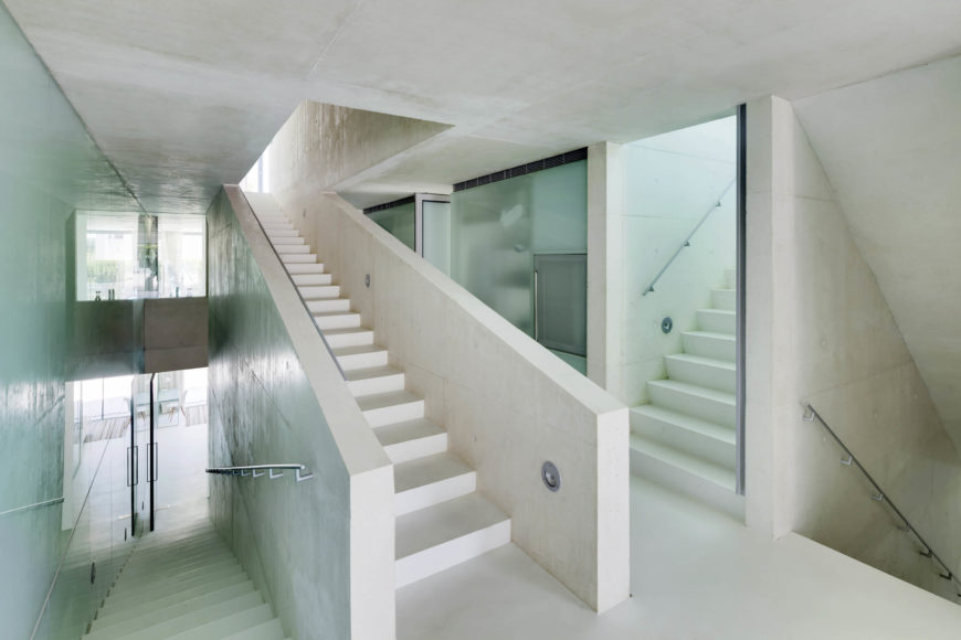 "Here's the central ""slow"" stair, winding through the center of the home. The mixture of white and aquamarine glass infuses the entire space with an airy calm."