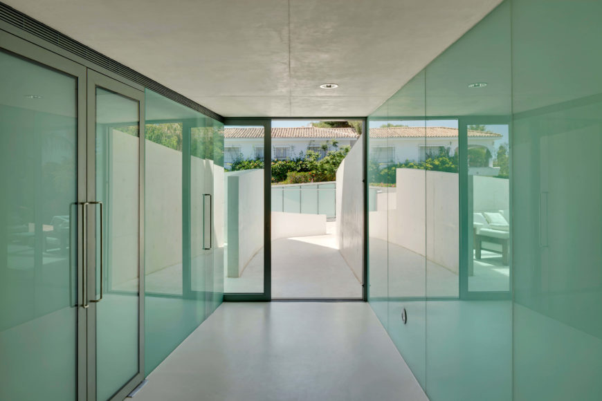 The main entrance opens into a glass-lined hall, reflecting and adding visual space between the white-hued floor and ceiling. Minimalism informs the entire space.
