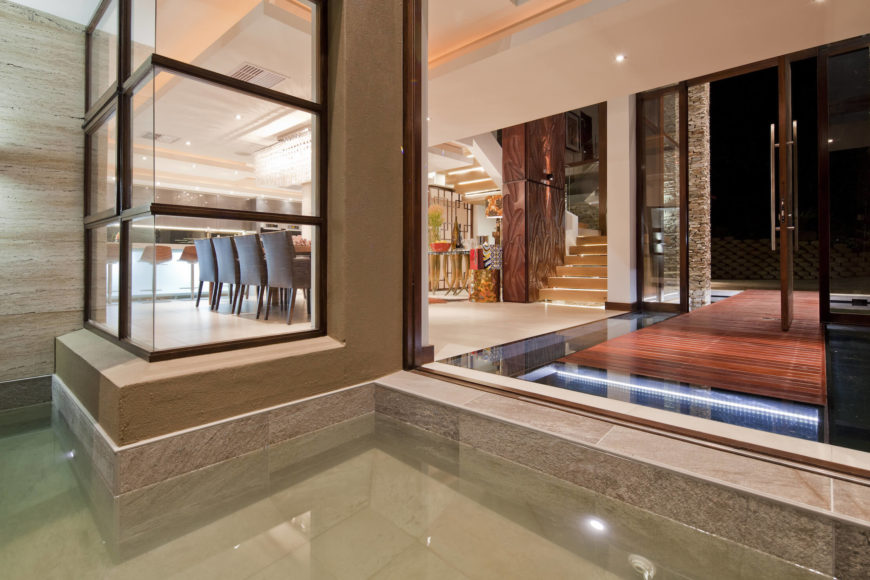 Looking into the entryway from the opposite side, we see the glass floor feature mirroring the water on the exterior.