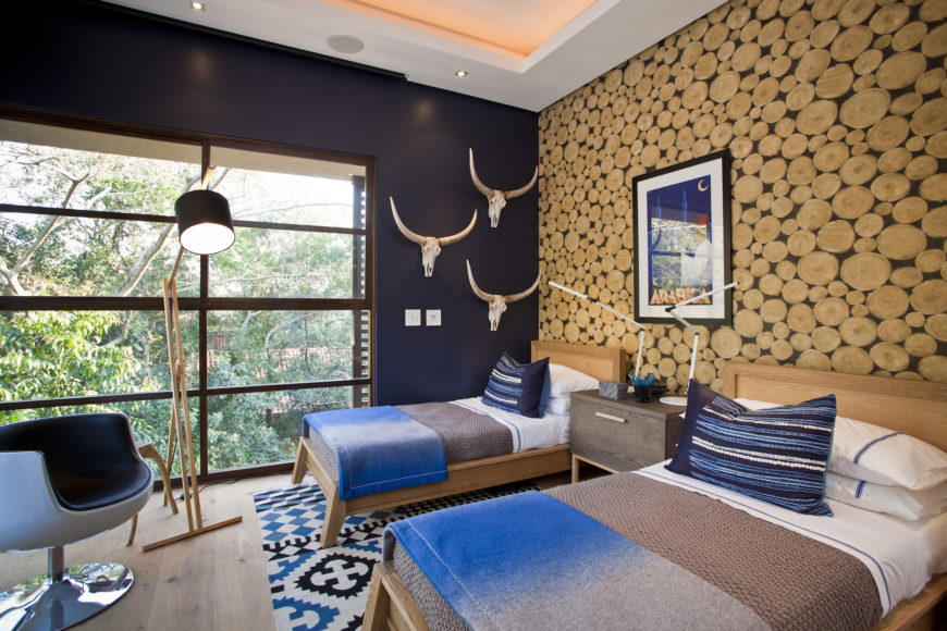This secondary bedroom features a bold stylistic break, with blue hues and circular wood cutouts on the wall, as well as a rustic look centered on the wood frame beds and unvarnished flooring.