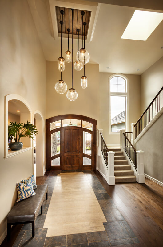 The entryway to the home is in both hardwood and tile. The staircase has two tight flights of stairs up to the upper level. The sidelights and transoms of the front door give it the illusion of being much larger than it is.