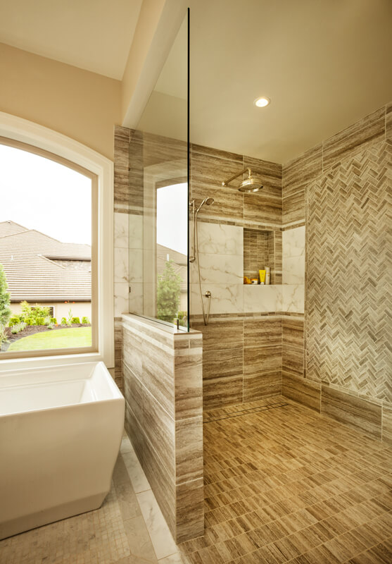 A closer look at the shower stall reveals the size of the shower, and the herringbone tile pattern on the back wall.