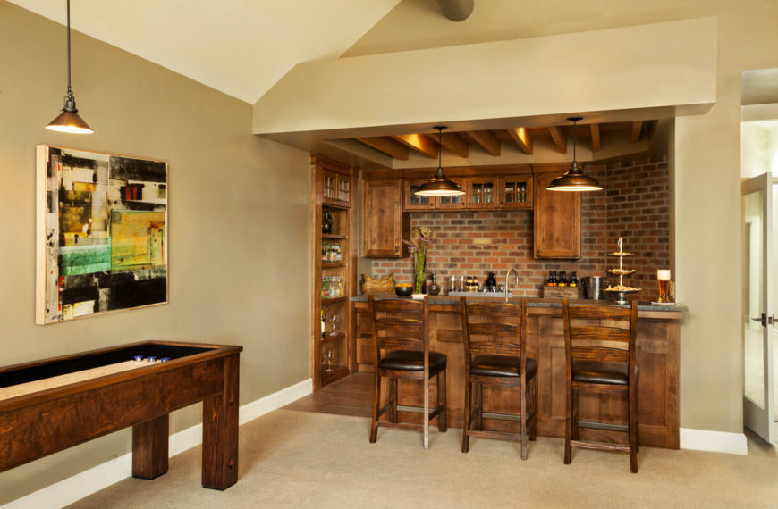 Behind the main television watching area is the home bar and a game table. The bar area is complete with an ice maker, dishwasher, and wine cooler.