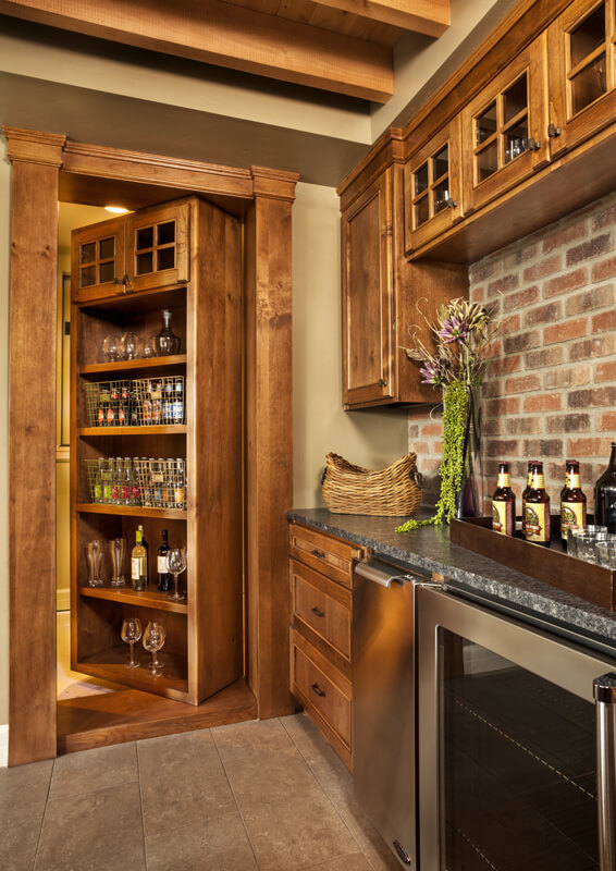 The built-in shelving swings open to reveal a hidden wine room.