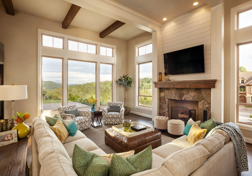 The light and bright living room has a large sectional in cream and two additional patterned armchairs. Two circular ottomans sit in front of the screened fireplace. The living room has soaring cathedral ceilings and enormous seamless windows.