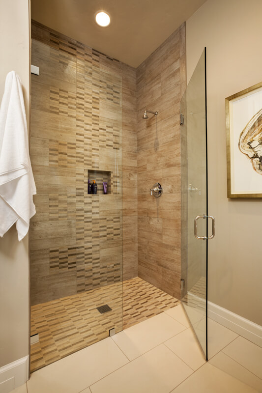The guest bathroom has a stone tile shower with a glass door. The bathroom is in a warm neutral beige.
