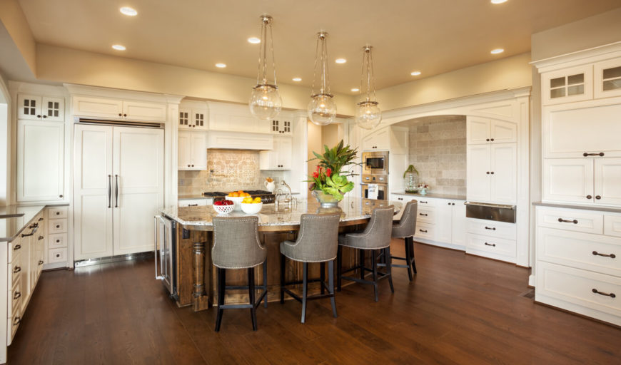 The expansive kitchen has plenty of counter space that allows multiple cooks to move freely around the kitchen. The three light fixtures above the kitchen island are simple glass globes. The ample white cabinetry takes advantage of the sheer size of the room.