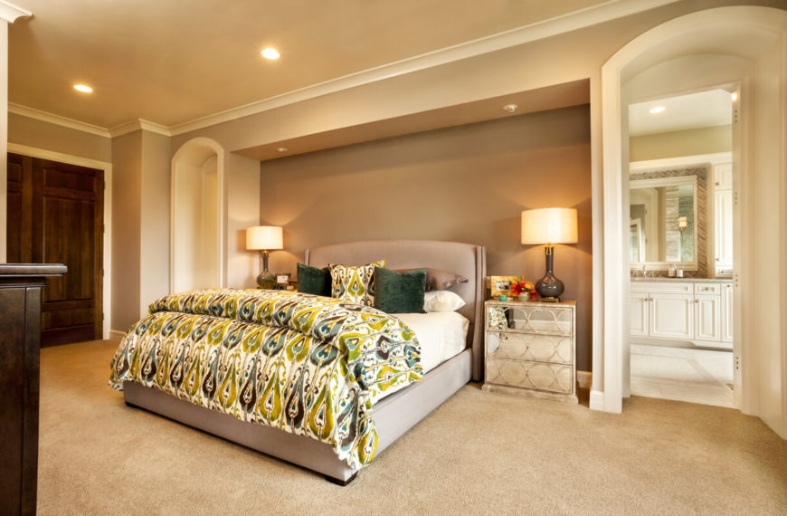The primary bedroom is in light neutrals, but brightens up the space with a green and teal peacock-print bedspread and throw pillows. The nightstand has a mirrored front with a circular pattern.