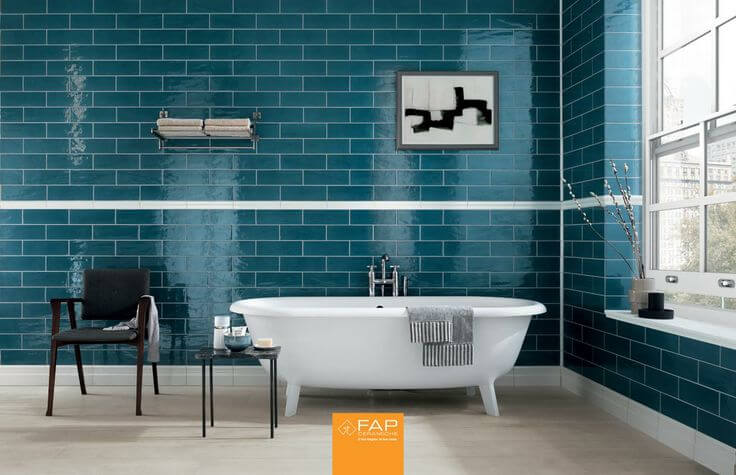 This bathroom boasts one of the brighter colors the tiles are available in: bright, deep blue. The blue tiles are broken up by a strip of white several feet from the white tiles that meet the floor.